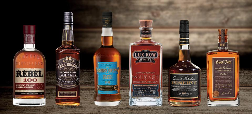 Six bottles of American whiskey are lined up end to end in front of a wooden barrelhouse.