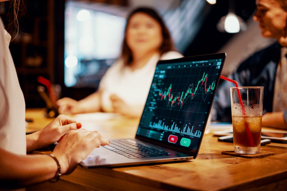 Mixed group of millennial aged friends discuss investing and cryptocurrency trading