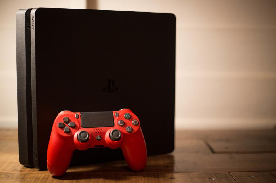 A Sony PlayStation 4 video game console with a red wireless...