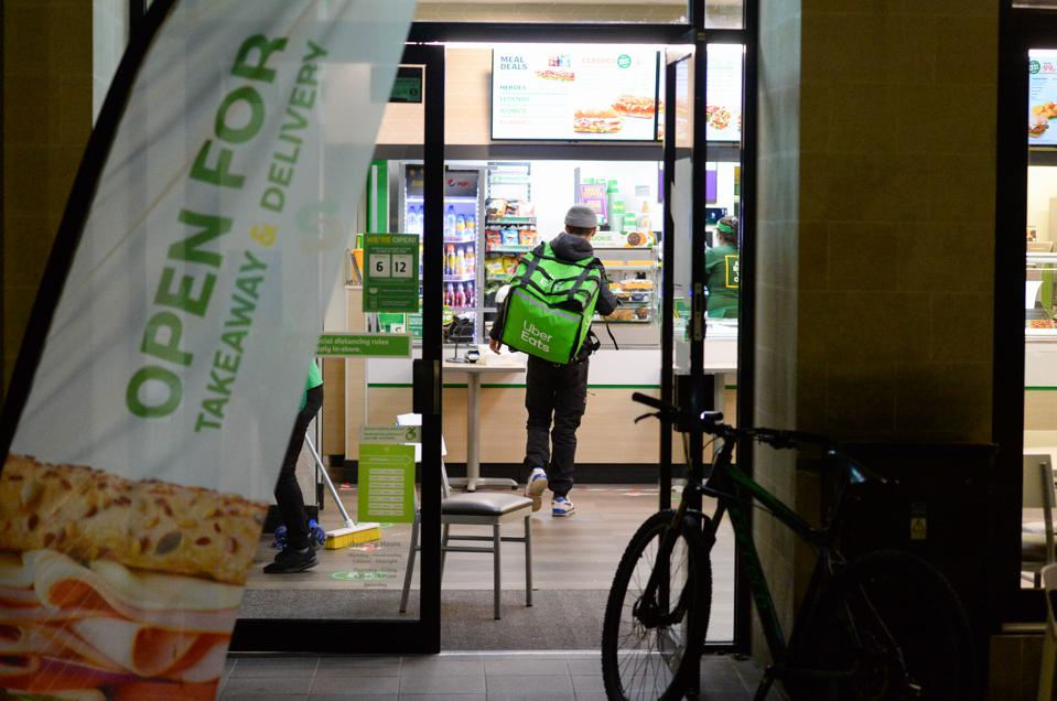 An Uber Eats delivery rider picks up an order from Subway on October 12, 2020 in Bristol, England, in tier 1.