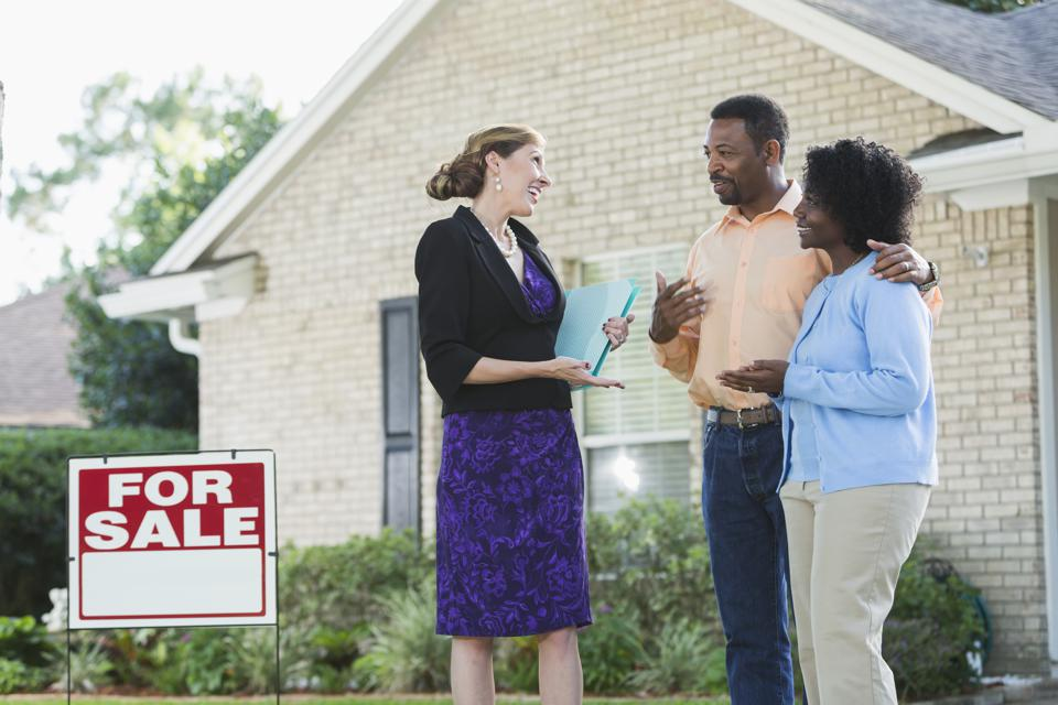Agent talking with couple in front of house for sale