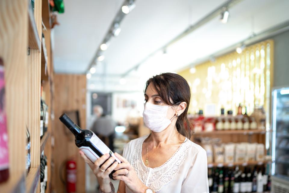 Senior woman buying wine with face mask at store
