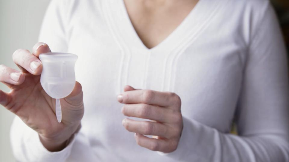 A person is holding a VOXAPOD menstrual cup in one hand.
