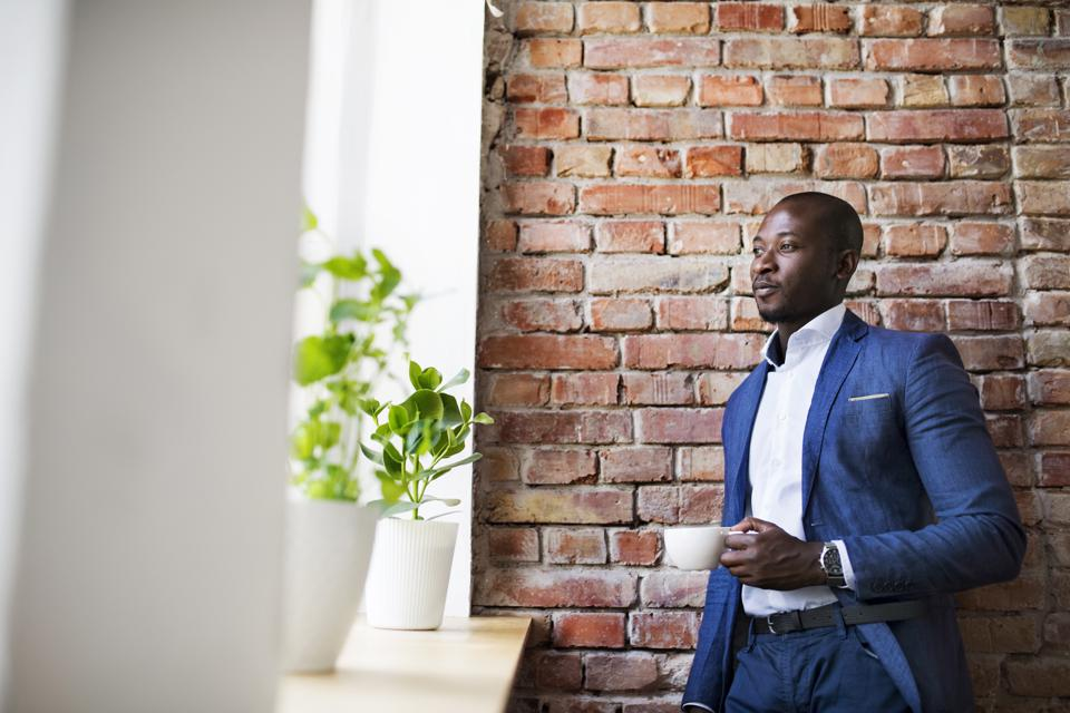 Businessman with cup of coffee at brick wall by the window
