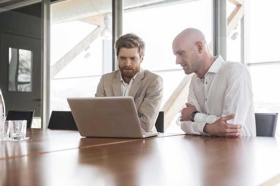 Two businessmen sharing laptop in conference room