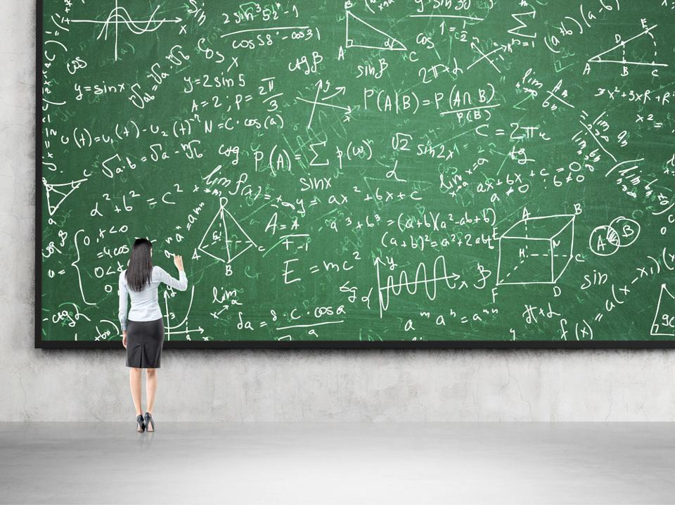 Woman standing in front of a chalkboard with math equations