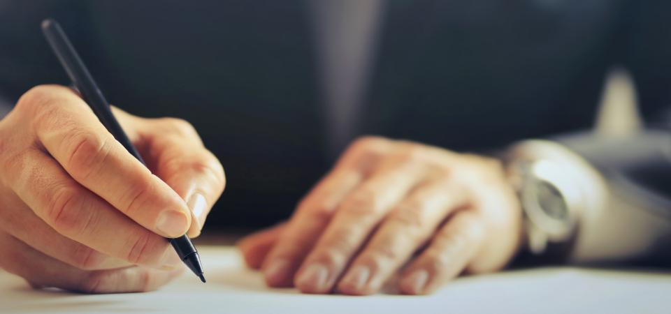 executive writing on paper