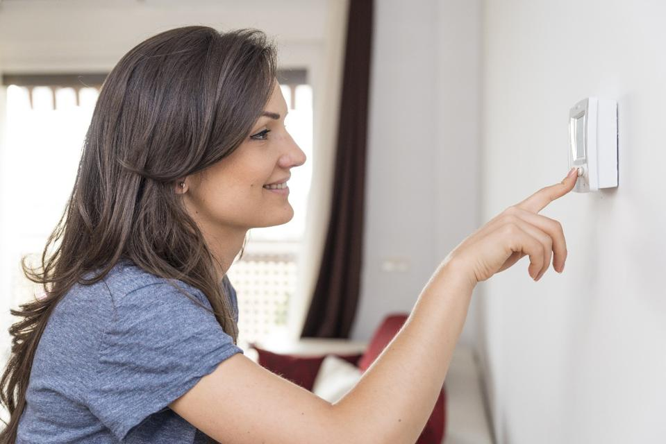 woman adjusting thermometer