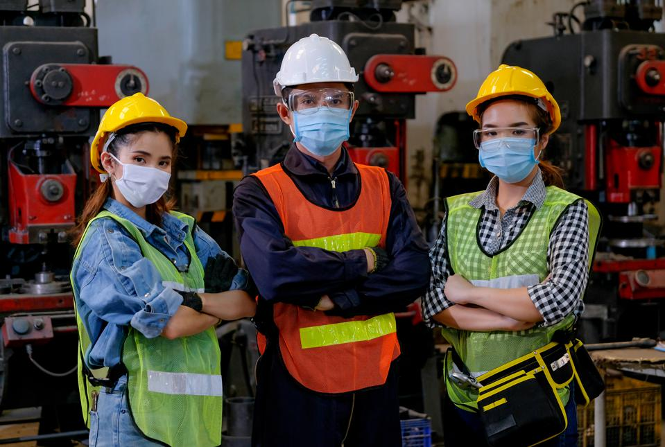 Group of man and woman workers with mask stand with confident action in the factory workplace and various machine as background
