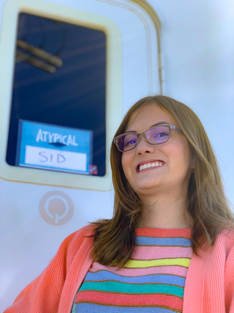 A woman with brown hair & glasses, poses in front of her trailer on the set of Atypical.