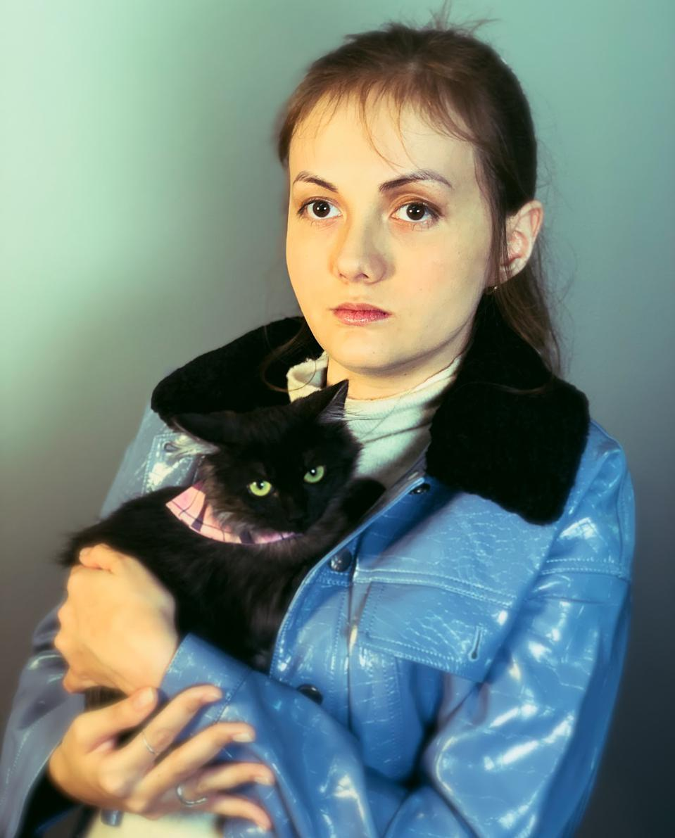 A woman with brown hair poses with her black cat.