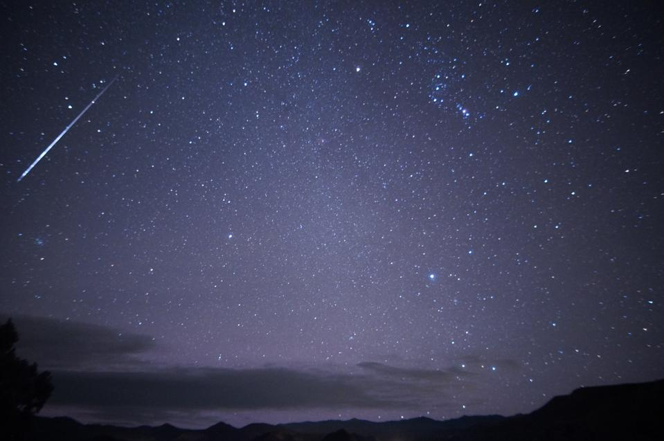 The constellation of Orion, visible in the upper right, with a bright Orionid meteor.