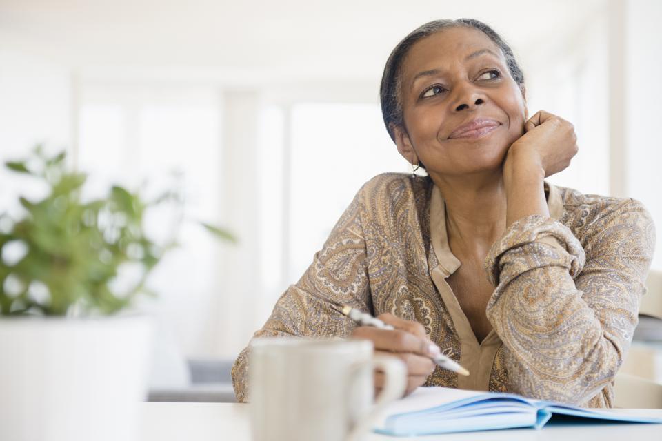 Mixed race woman writing at desk