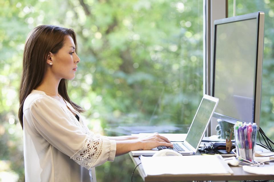Mixed race businesswoman working on laptop in office