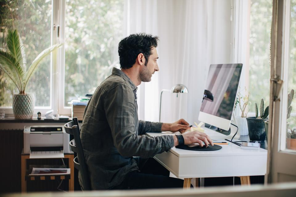 Side view of young businessman using computer while sitting at desk in home office