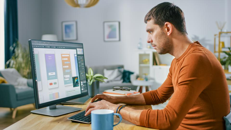 Handsome Software Engineer Works on a UX / UI Mobile App Template, Uses Personal Computer. Freelance Programmer Working At Home from Cozy Living Room.