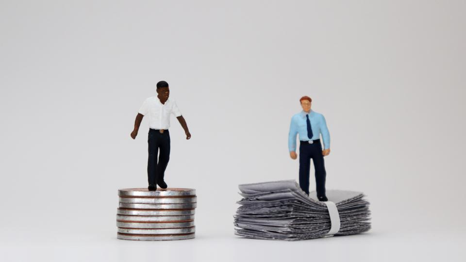 The concept of racial wage discrimination in a company. Money and two miniature people.