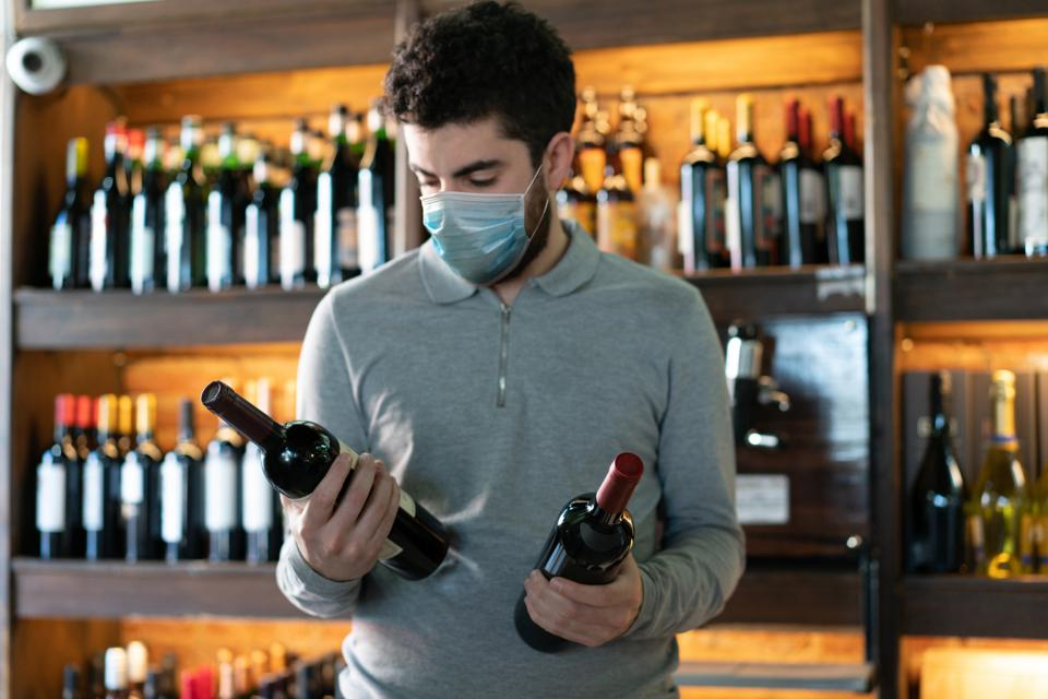Young man at a wine cellar choosing between two wine bottles wearing a protective face mask