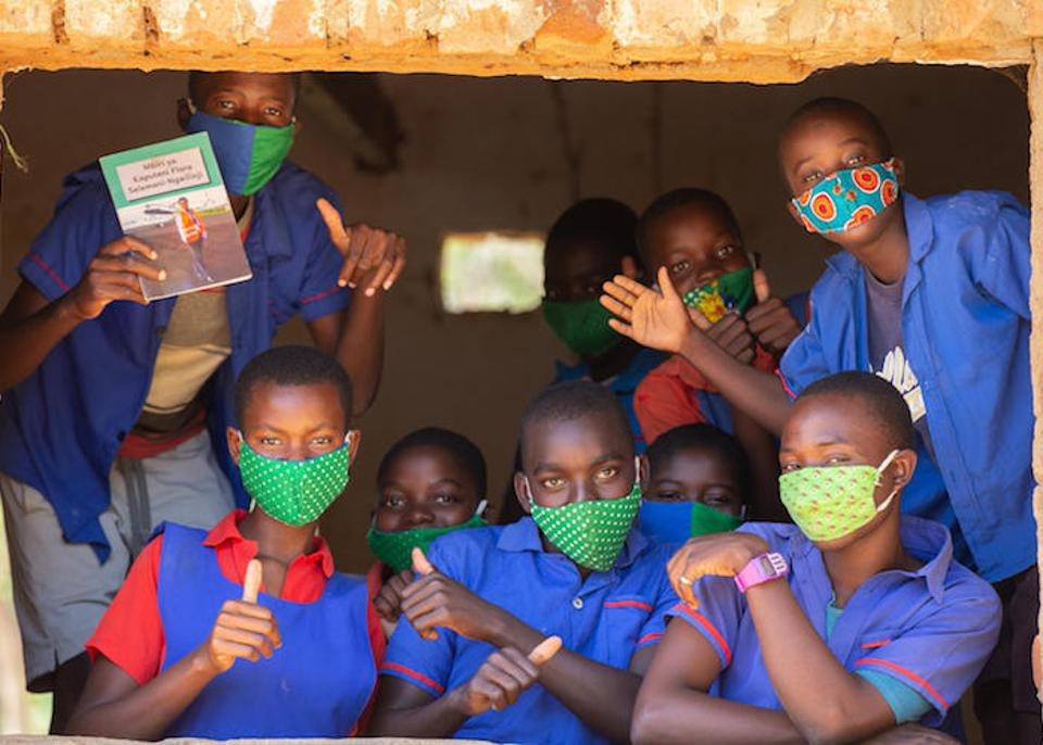 Students happy to be back at school peer out from a classrom window at Luwambaza primary school in Malawi on September 24, 2020.
