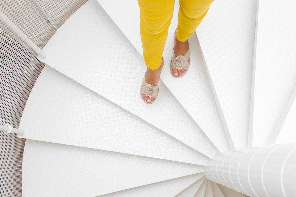 Young woman's legs in yellow trousers and sandals going down on white spiral stairs. Top view.
