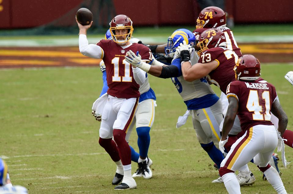 LANDOVER, MD - OCTOBER 11:  Alex Smith #11 of the Washington Football Team is hit by Aaron Donald #99 of the Los Angeles Rams after throwing a pass in the second quarter at FedExField on October 11, 2020 in Landover, Maryland.