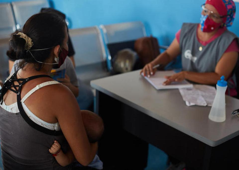 Above, a mother who recently returned from Colombia with her two sons meets with a counselor at the UNICEF-supported Integral Care Center in Táchira.