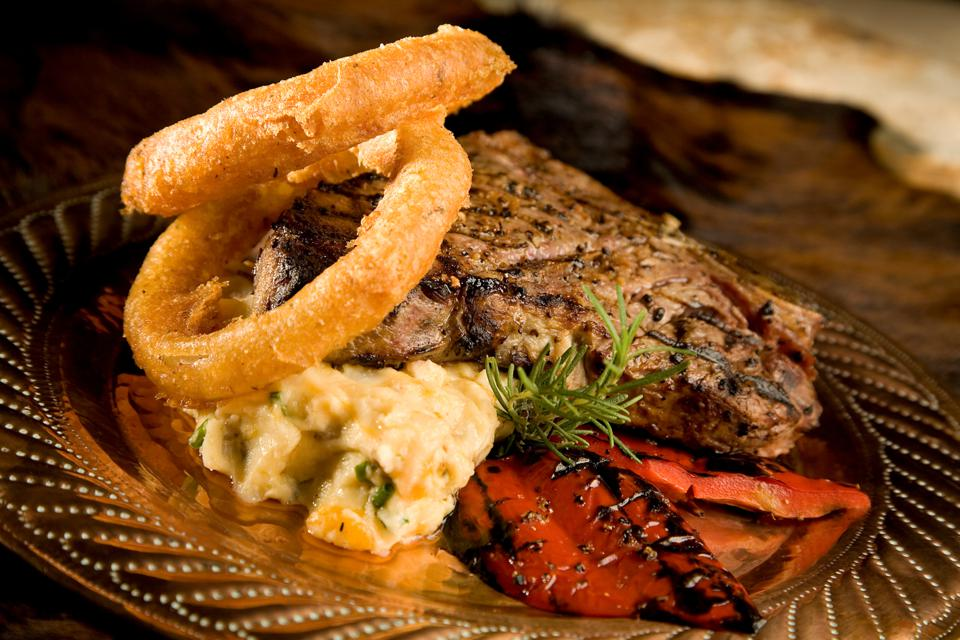 Grilled steak with onion rings and roasted red peppers.