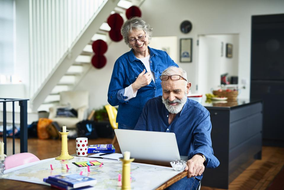 Cheerful retired couple at home planning vacation and man using laptop