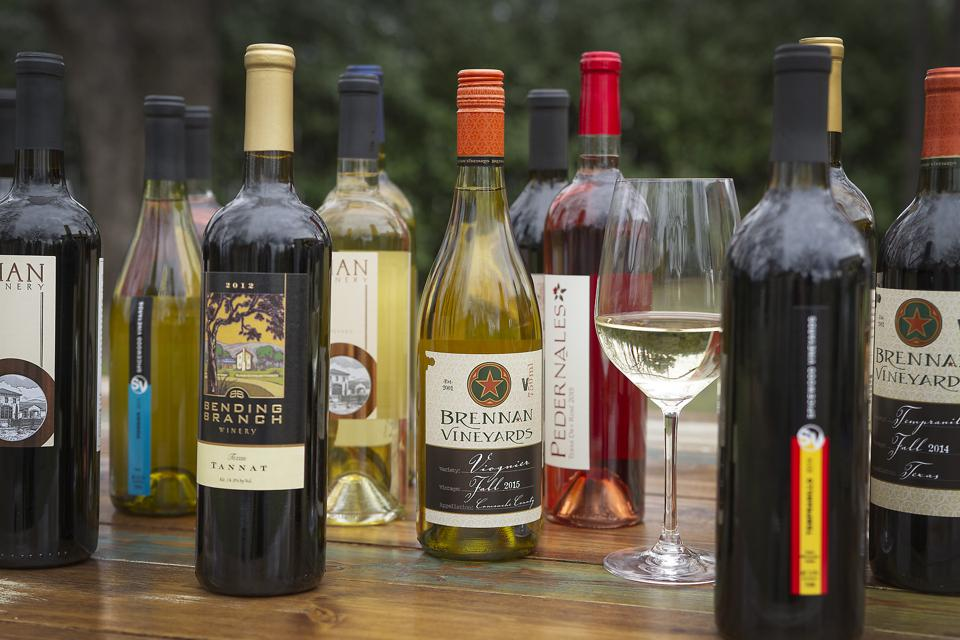 Various bottles of Texas wine in outdoor setting.