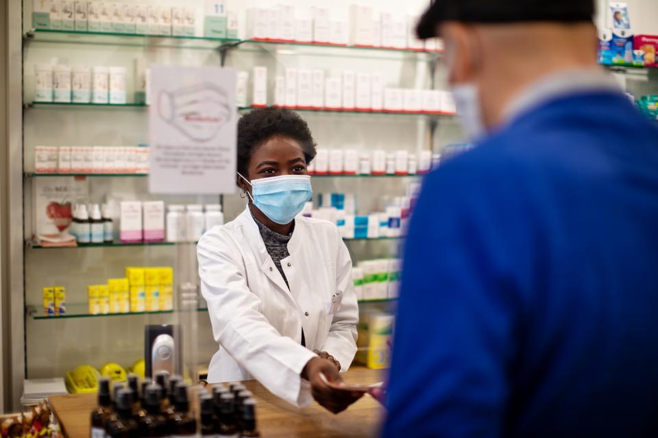 Pharmacist selling medicine to senior man