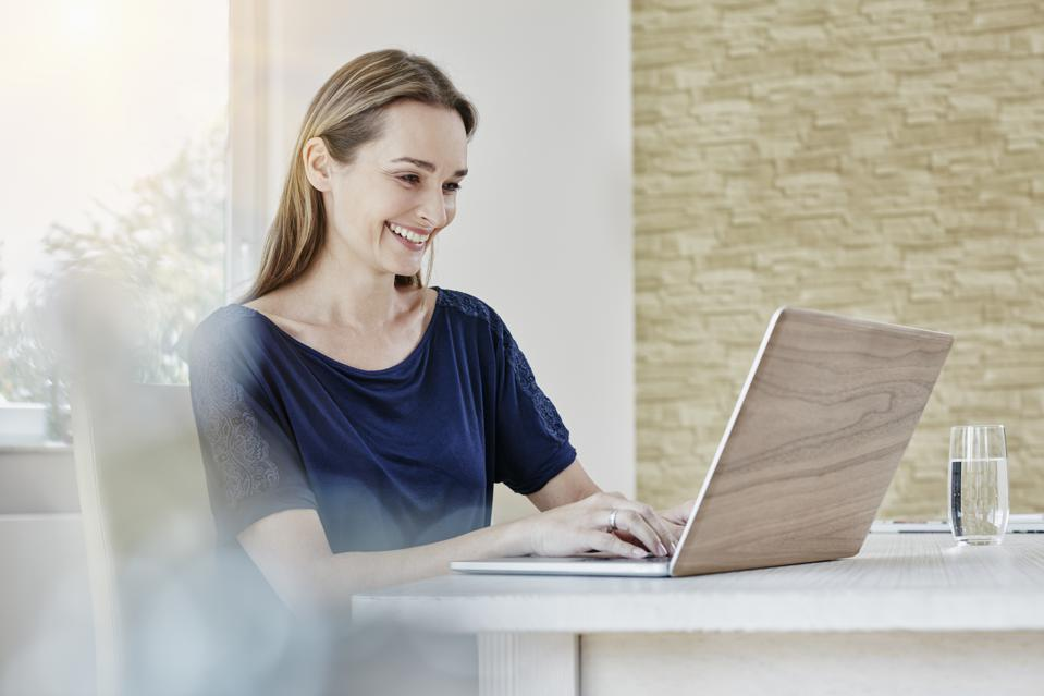 Happy woman at home using laptop