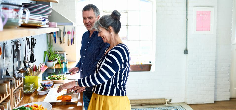Mature couple preparing vegetarian meal in stylish kitchen