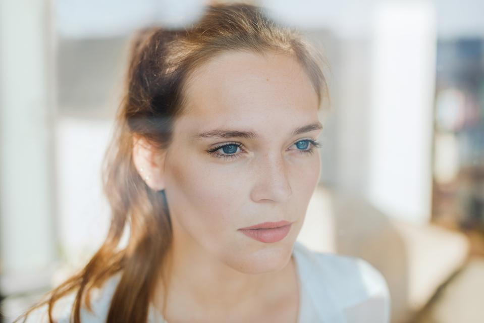 Woman looking serious behind a window.