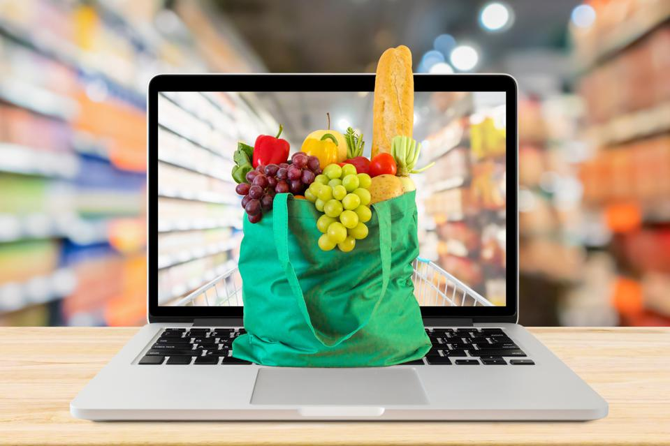 supermarket aisle blurred background with laptop computer and green shopping bag on wood table grocery online concept