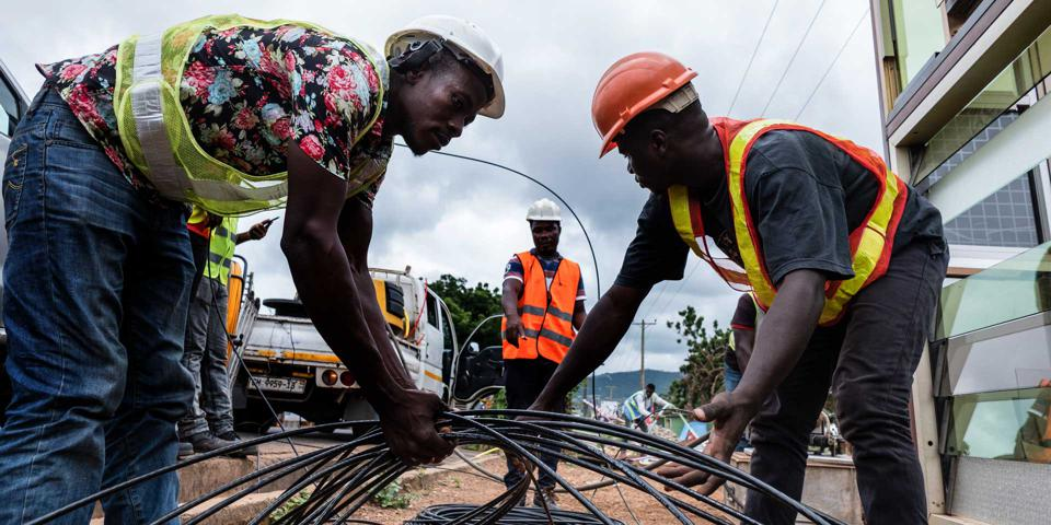 African men in hard hats lay down fiber wire under the supervision of a manager