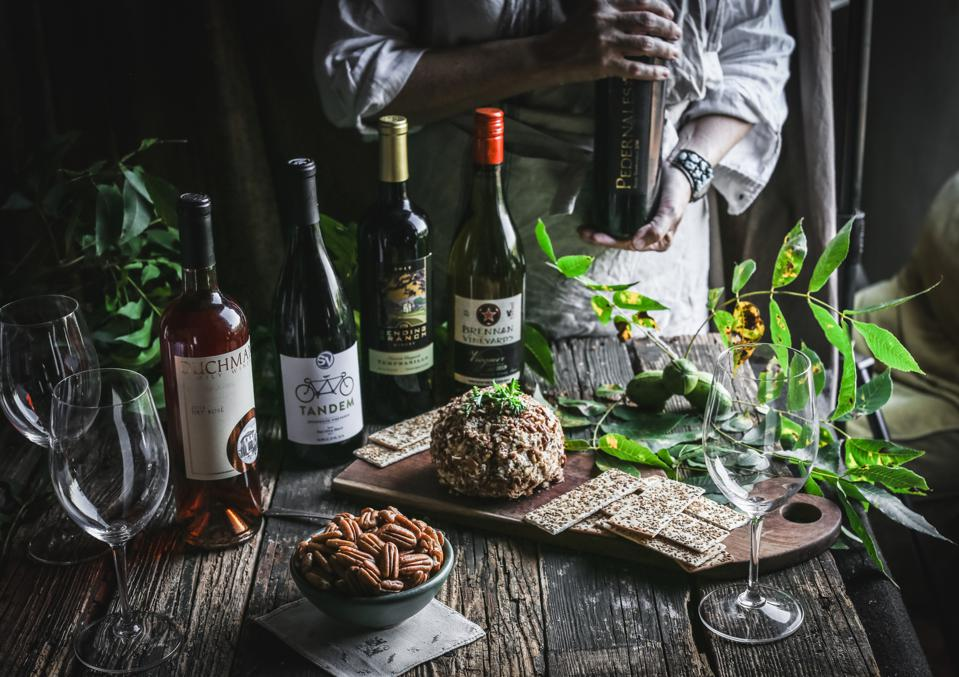 Bottles of wine and plate of pecans on a rustic wooden table.