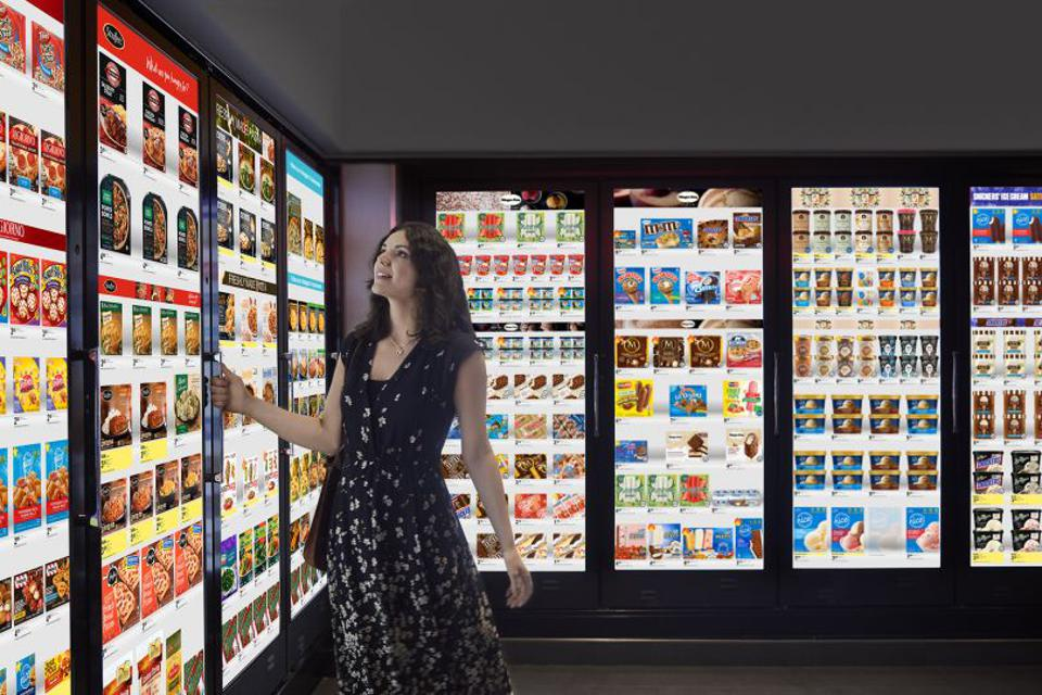 A woman interacting with Cooler Screens in a retail setting