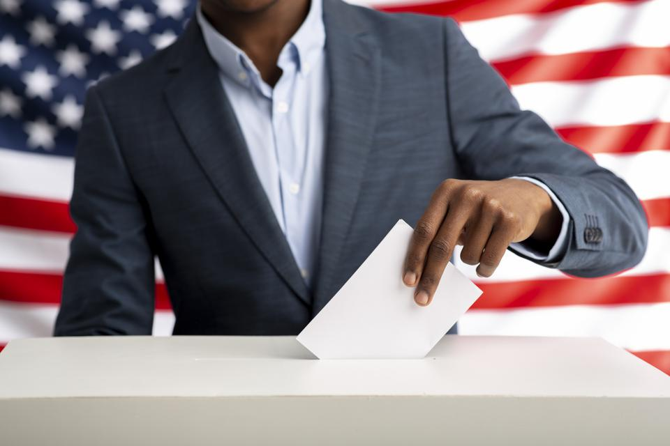 African american man holds envelope in hand above vote ballot