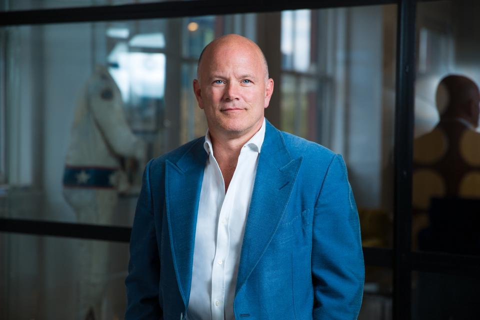 Mike Novogratz, wearing a white shirt and teal suit jacket, stands before a glass wall