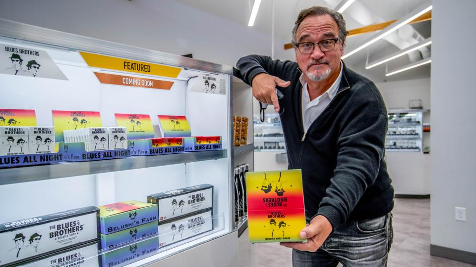Jim Belushi inspecting his Blue Brothers pre-rolls on shelves at The Green Solution.