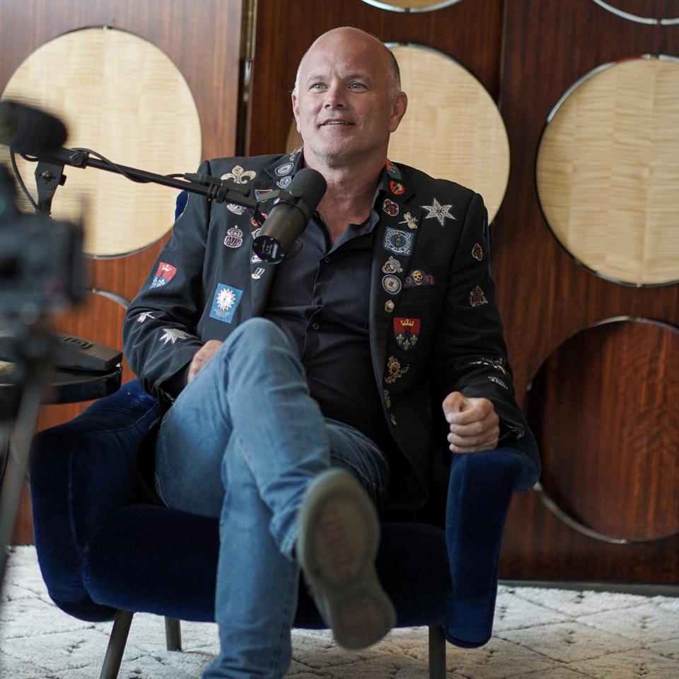 Mike Novogratz sitting in low chair with microphone in front of face during interview