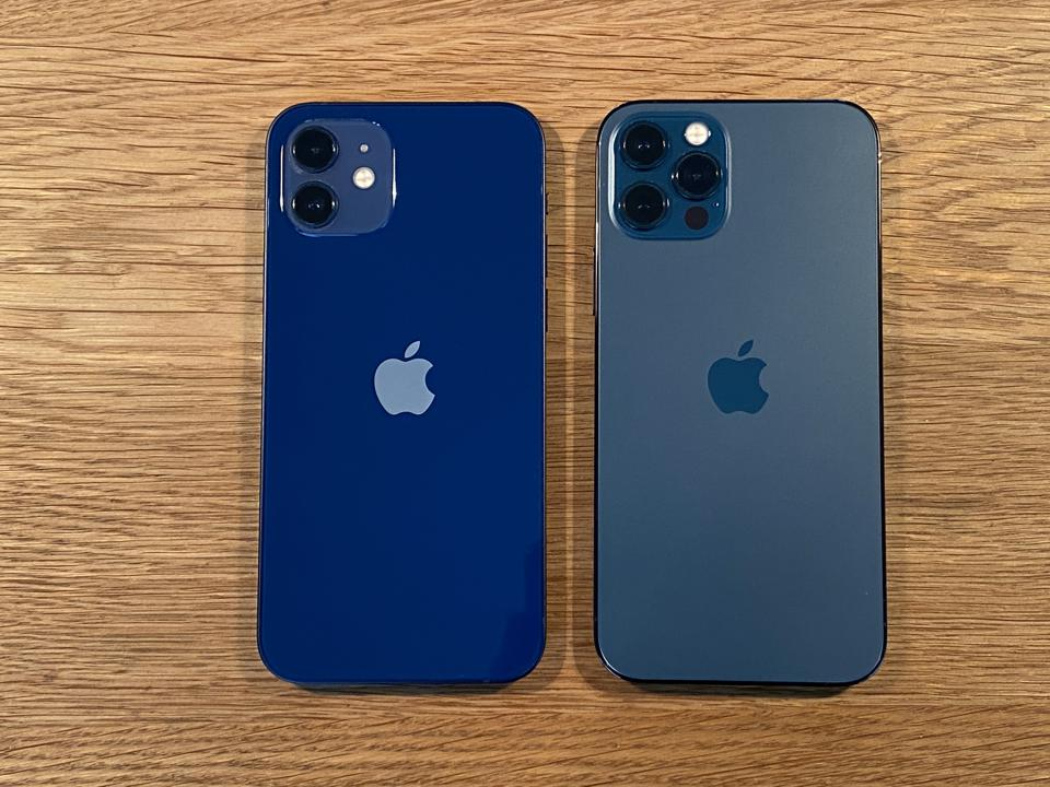 Side by side: the shiny iPhone 12, left and matte iPhone 12 Pro, right.
