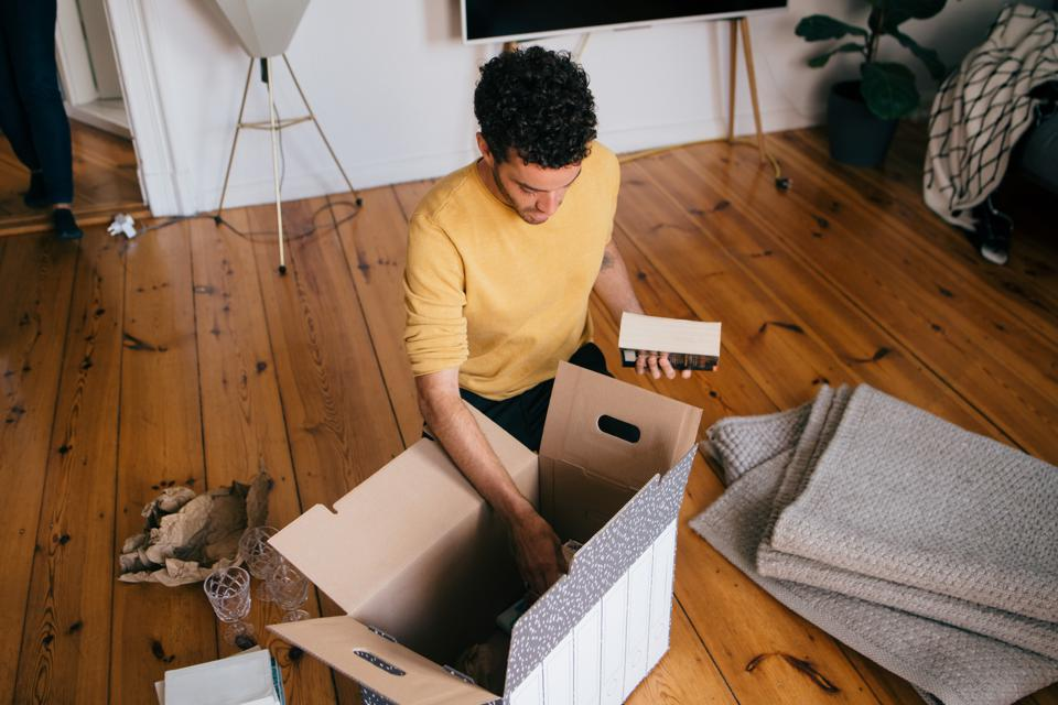 High angle view of man removing novels from cardboard box at new home