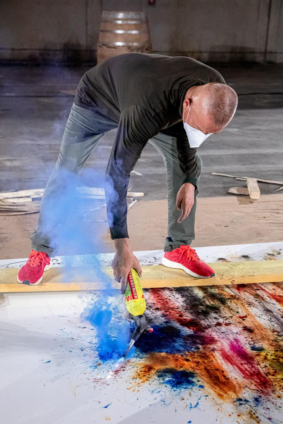 Cai Guo-Qiang working on a colored gunpowder painting that is now part of Hennessy's permanent collection