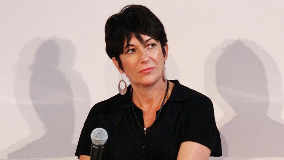 Ghislaine Maxwell wearing black holding microphone.