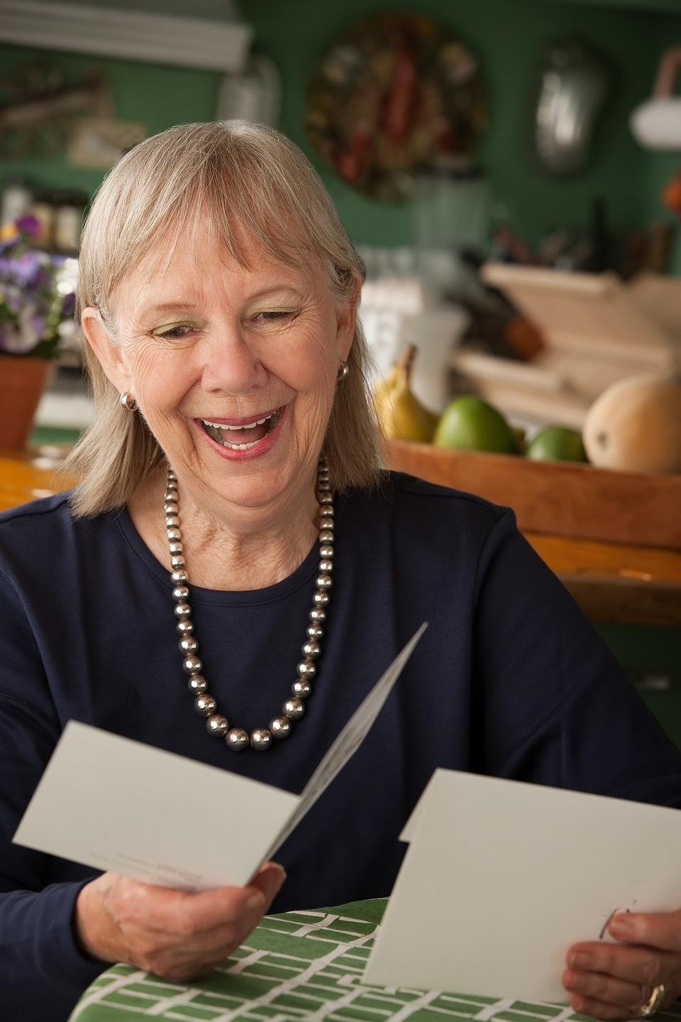Mujer sonriente mirando una tarjeta de alguien que le gusta