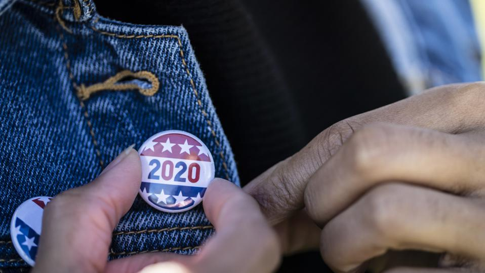 young African American woman, with election 2020 pin on her jacket