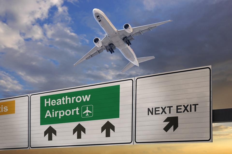 Road sign indicating the direction of Heathrow airport and a plane that just got up.