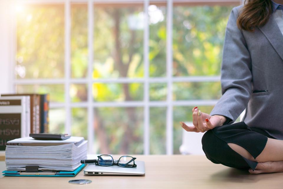 business woman relaxing meditating in office, peaceful ceo in suit practicing yoga at work