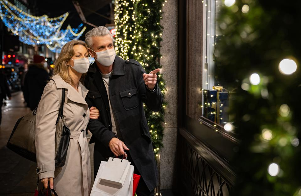 Couple Christmas shopping wearing a facemask in London